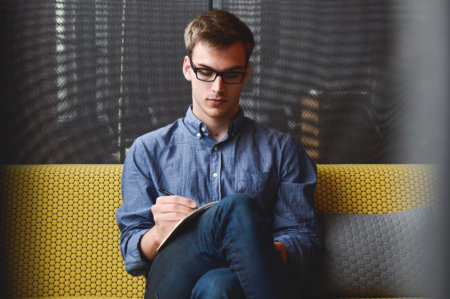 Picture of a man with glasses sitting on a yellow bench filling out paperwork.